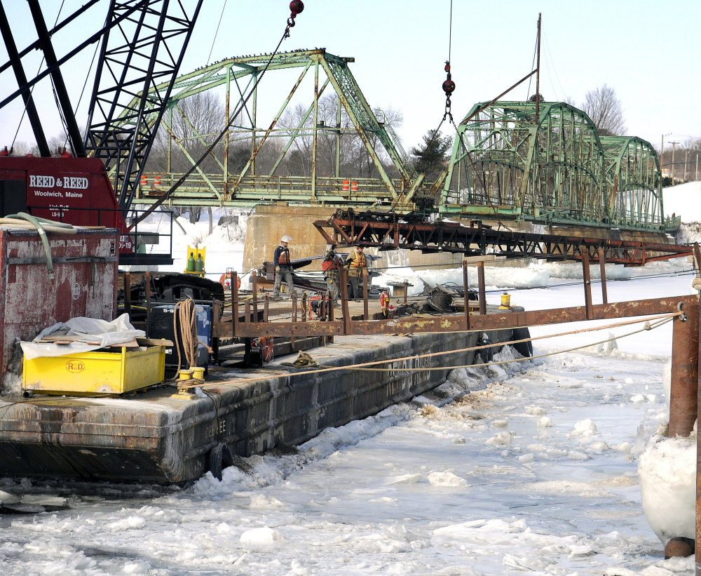Reed & Reed contractors move equipment Monday between a pier on the Kennebec River in Dresden and a raft with a crane used to raze the old bridge that spanned the river between Richmond and Dresden. Reed & Reed is dismantling the existing five-span steel truss bridge and bridge piers that supported it.