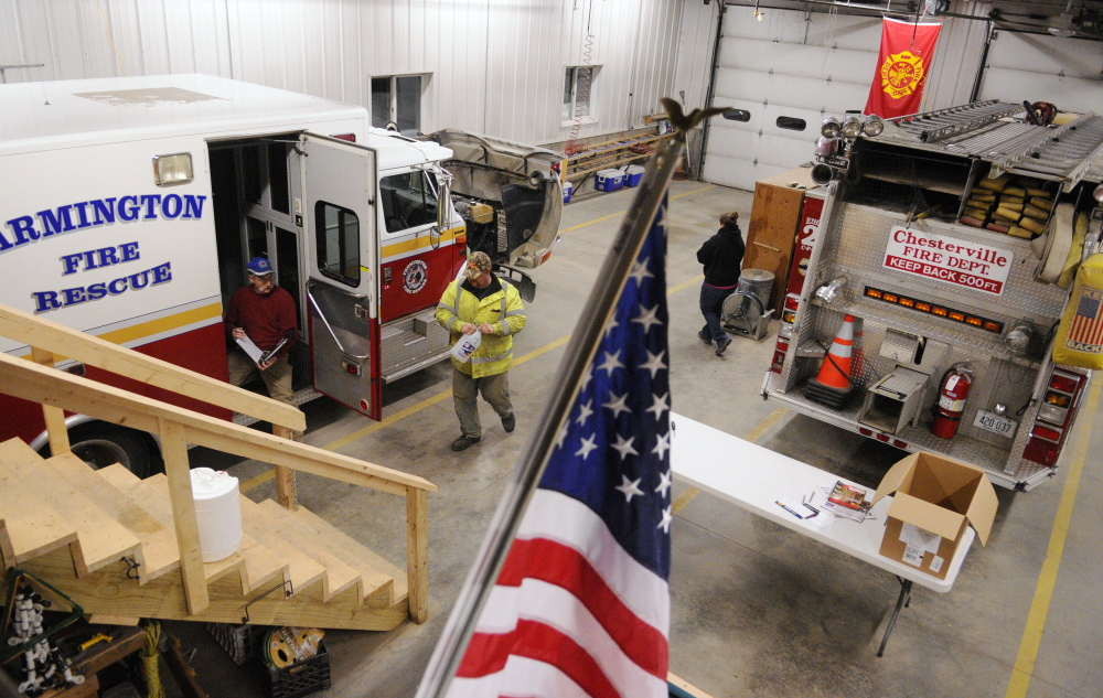 Chesterville firefighters inspect one of the department's fire rescue trucks recently at the fire station in Chesterville. Central Maine departments are feeling the crunch of fewer volunteers, less money and more required training.