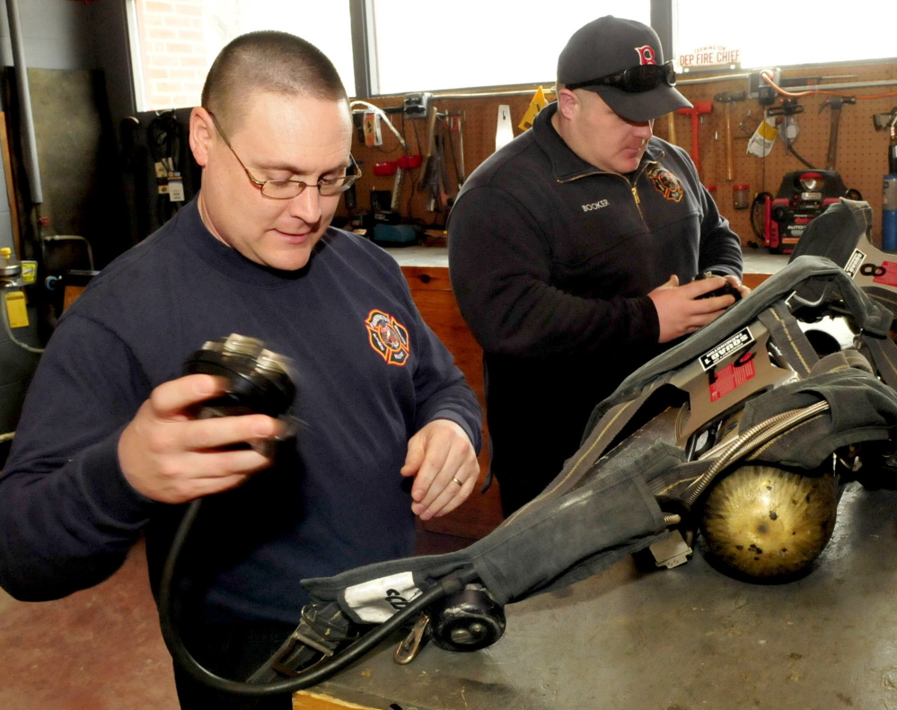 Farmington firefighters Kyle Ellis, left, and Mike Booker conduct a daily inspection of air packs recently at the Farmington Fire Department.