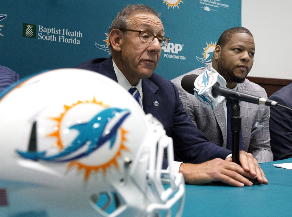 Miami Dolphins owner, Stephen Ross, left, and his newest player, Ndamukong Suh, talk Wednesday in Davie, Fla.. Suh signed a $114 million, six-year deal with the Dolphins.