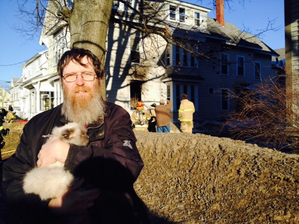 Peter Beach, a resident of 58 Silver St. in Waterville was among the residents forced to leave the building when fire broke out Friday afternoon. Beach left with his cat, China, while firefighters went to work in the building, in the background.