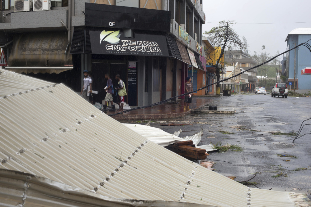 People walk past debris scattered on a street in Port Vila, Vanuatu, on Saturday in the aftermath of Cyclone Pam. Winds from the extremely powerful cyclone that blew through the Pacific's Vanuatu archipelago are beginning to subside, revealing widespread destruction.