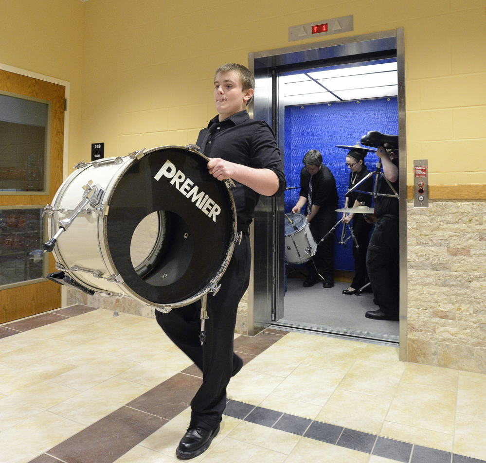 SOUTH PORTLAND, ME - MARCH 14: Ellsworth HS drummer Cameron Petros, a sophomore, carries one of his drums from a crowded elevator to the stage as they get ready to compete at the 2015 MMEA High School Instrumental Music Jazz Festival at South Portland HS. (Photo by John Patriquin/Staff Photographer)