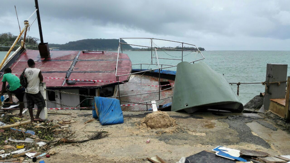 Locals stand by a tilted boat in Port Vila, Vanuatu, on Sunday after Cyclone Pam ripped through the tiny South Pacific archipelago.
