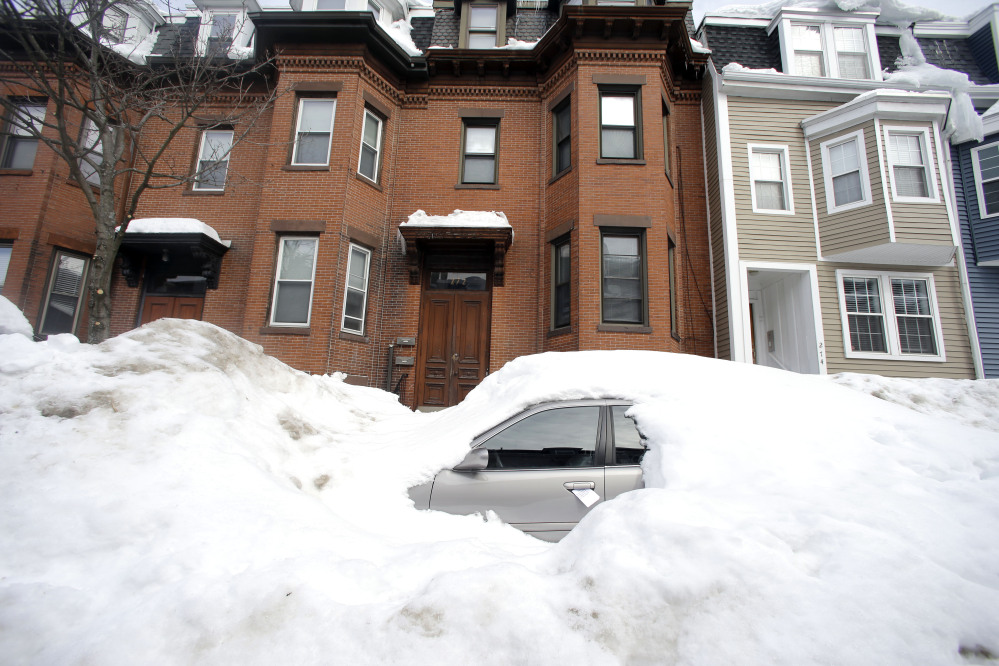 In this Feb. 23, 2015 file photo, a car remains buried in snow along a residential street in South Boston. Boston's miserable winter is now also its snowiest season going back to 1872.