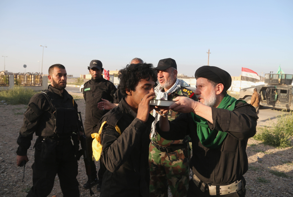 A young volunteer kisses the Quran, the Muslim holy book, as a Shiite cleric blesses him before going into battle against Islamic State fighters in Tikrit, 130 kilometers (80 miles) north of Baghdad, Iraq, Sunday.