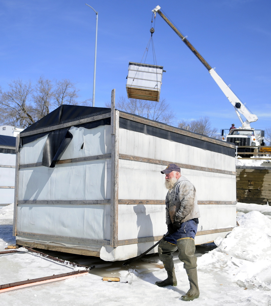 Jimmy Worthing levers a smelt camp off the ice Monday on the Kennebec River in Randolph as another shack is hoisted to shore. Worthing's Smelt Camps removed 20 of the shacks from the ice but plans to keep several available for fishermen.