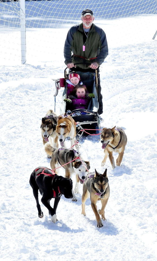 """Musher Kevin Quist, of Heywood Kennel in Augusta, and his team of dogs take Cornville Regional Charter School students Maddy Thorndike, left, and Isabella Mullen for a ride at the school on Monday. """"That was cool,"""" both girls shouted at the end of the ride."""