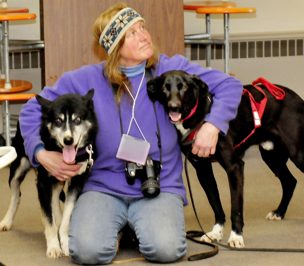 Musher Lindy Howe, of Heywood Kennel in Augusta, holds two of her sled dogs at the Cornville Regional Charter School during a demonstration on Monday.