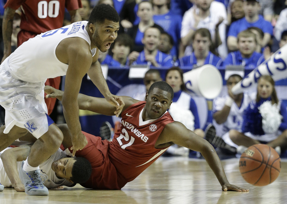 Kentucky guard Andrew Harrison (5) and Arkansas guard Manuale Watkins (21) chase a loose ball during the second half of the Southeastern Conference championship game Sunday in Nashville, Tenn. The Wildcats are the heavy favorites to win the NCAA tournament.