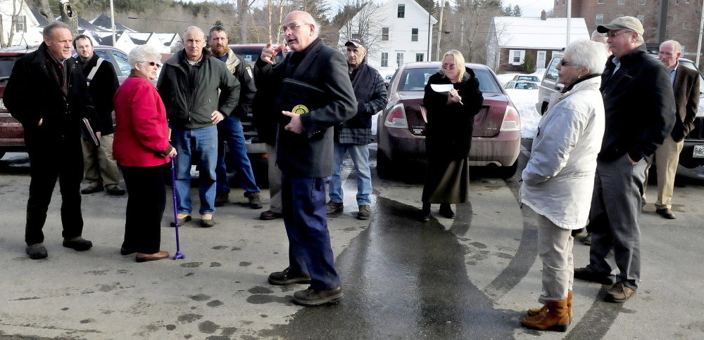 Farmington Planning Board Chairman Clayton King, center, directs other board members and interested citizens to where a tractor-trailer will negotiate a turn to deliver wood chips to a proposed wood boiler system on the University of Maine campus on Monday.
