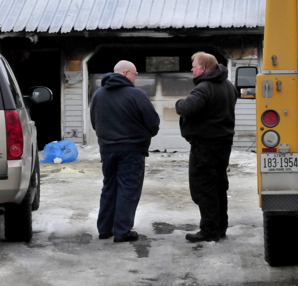 Ken MacMaster, left, of the state Fire Marshal's Office and Bart Newhouse of the state Department of Environmental Protection investigate a fire that destroyed a home on Dinsmore Road in Sidney Monday evening.