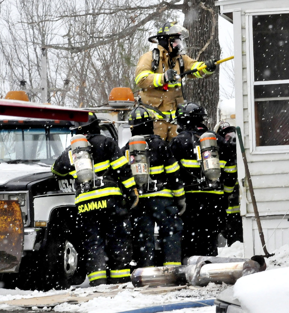 Firefighters use tools to open up walls and roof to get to fire that did serious damage to a home on Crummett Street in Benton on Tuesday. Firefighters tore off sections of metal chimney section on ground.