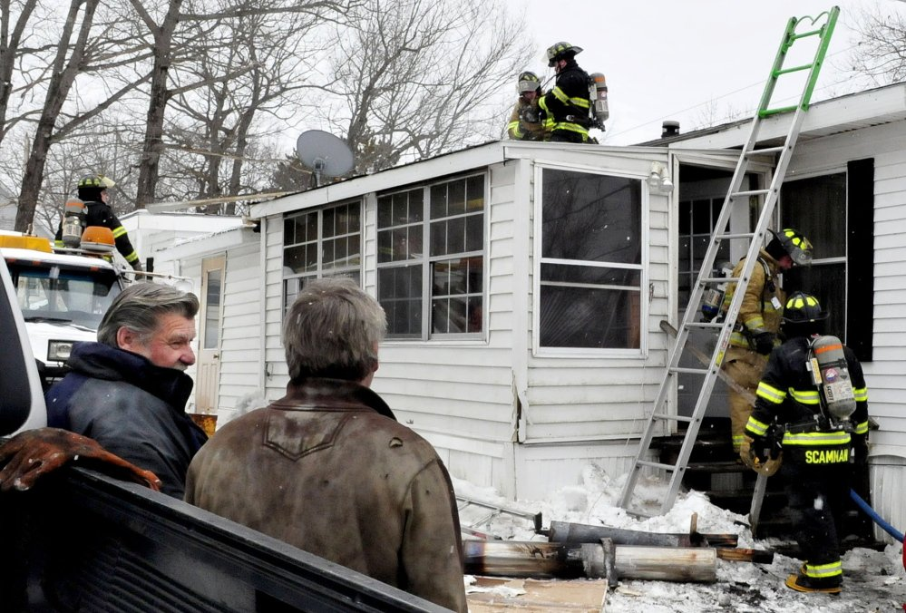 Business and homeowner Gary Bulger, left, speaks with a friend as firefighters from Winslow and Fairfield departments extinguish a stubborn fire in a home on Crummett Street in Benton on Tuesday. The address was site of another fire in which a car garage was destroyed a decade ago.