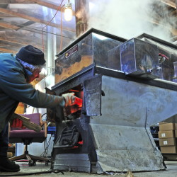 Bob Bacon loads more wood into an evaporator Friday at Bacon Farm Maple Products in Sidney. It was the first day this season the business boiled, according to Shelley Bacon, who said March 13 is a little later than normal. The farm, at the corner of Route 23 and Goodhue Road, has been in the same family and making maple syrup since 1881. Besides selling syrup made there, the owners also sell equipment and supplies to other producers.