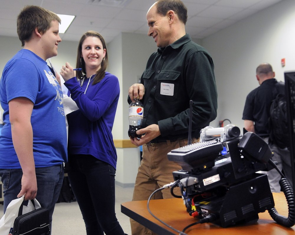 Office of Information Technology employee Marc Fisher helps Monmouth Academy students Andrew Reny, left, and Jenna Brown with questions on Thursday at the Maine Office of Information Technology's annual Tech Night in Augusta. Fisher and his colleague, John Covert, displayed the state's new public safety radio system to students.