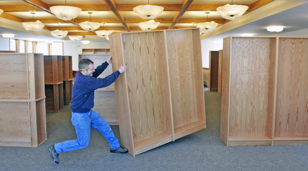 After assembling shelves, Jamie Clough, owner of JC Millwork, positions them in the new addition under construction at the C.M. Bailey Library in Winthrop on Thursday.