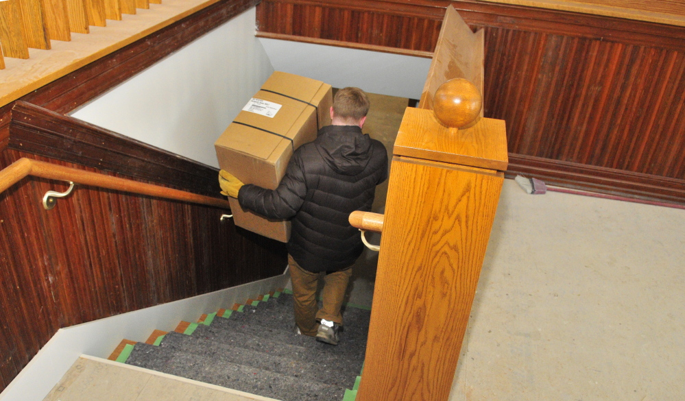 Library director Richard Fortin carries equipment to the basement of the new addition under construction at the C.M. Bailey Library in Winthrop on Thursday. The wainscoting and trim on the walls in the photo was repurposed from the old Masonic Temple that was demolished to make room for the new addition.