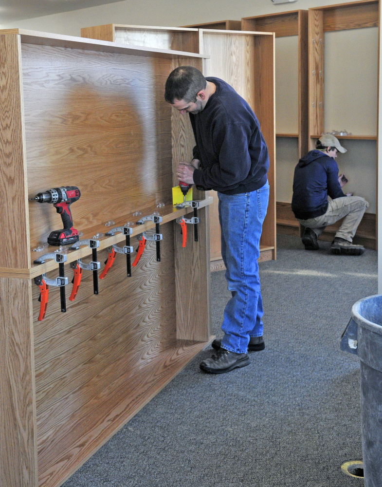 Jamie Clough, owner of JC Millwork, left, and Caleb Castonguay assemble shelves in the new addition under construction at the C.M. Bailey Library on Thursday in Winthrop.