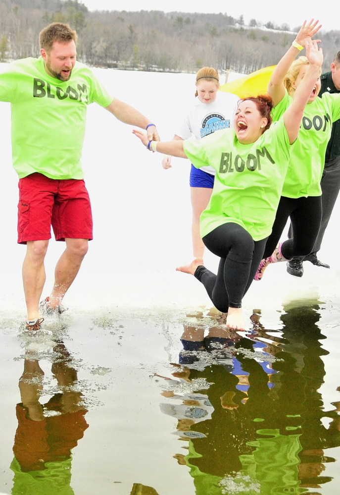 Green-shirted Team Bloom members Corey Rubchinuk, left, Kayla Diplock and Kim Stoneton leap into Marancook Lake during last year's Ice Out Plunge at the town beach in Winthrop.