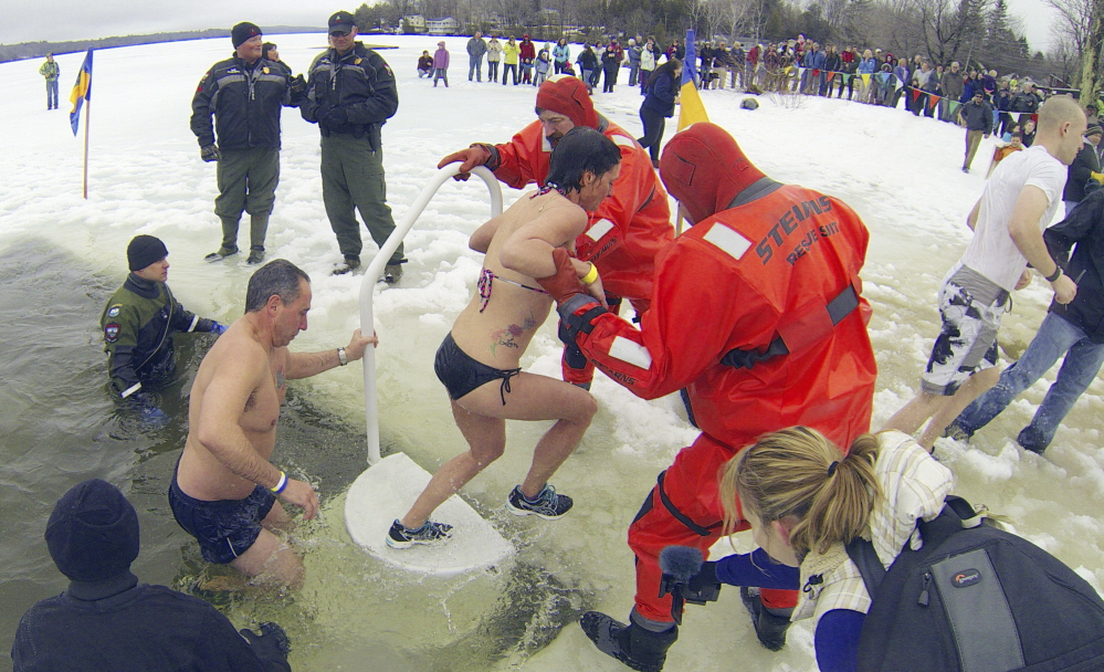 Plungers climb out of a hole in the ice after jumping into Maranacook Lake during last year's Ice Out Plunge at the town beach in Winthrop.