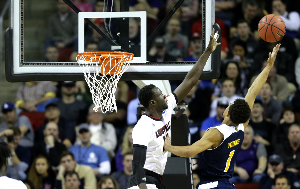 Louisville's Mangok Mathiang, left, tries to block a shot by UC Irvine's Alex Young, right, in the second half Friday of an NCAA tournament game in Seattle. Louisville beat UC Irvine 57-55.
