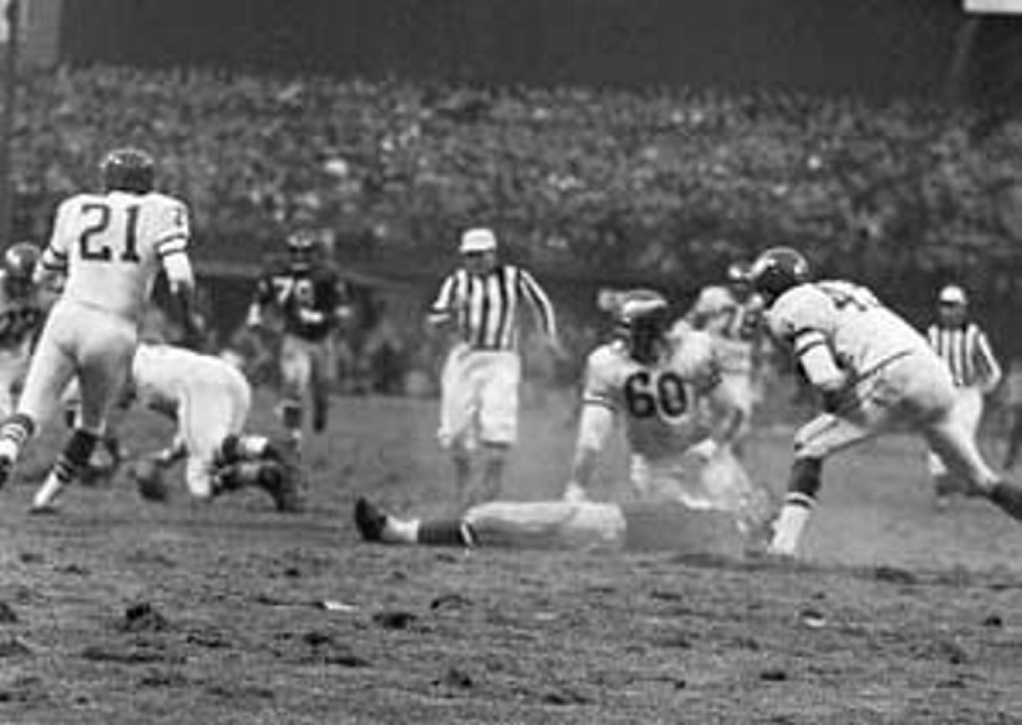 New York Giants' Frank Gifford lies on field as play continues after he was knocked unconscious by Philadelphia Eagles' Chuck Bednarik, 60, in a 1960 game at Yankee Stadium. Bednarik, a Pro Football Hall of Famer and one of the last great two-way NFL players, has died. He was 89.