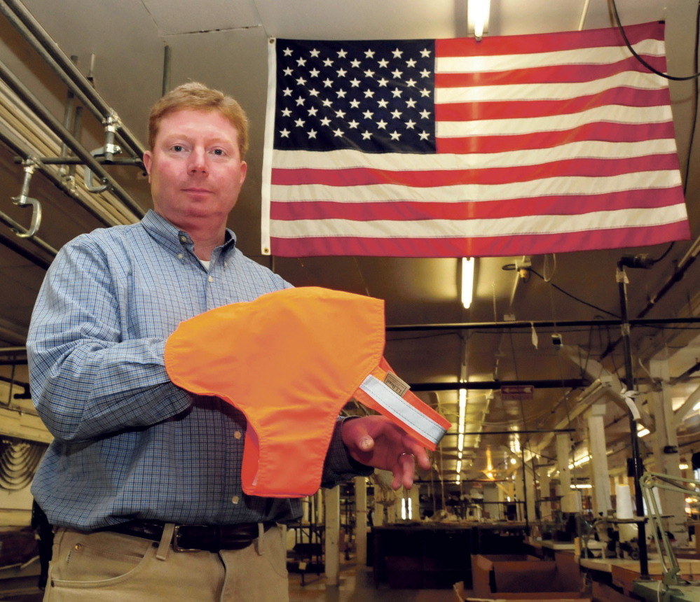Bill Swain, owner of Maine Stitching Specialties in Skowhegan, holds an L.L. Bean No Fly Zone dog vest beside and American flag made at the Skowhegan company on Wednesday.
