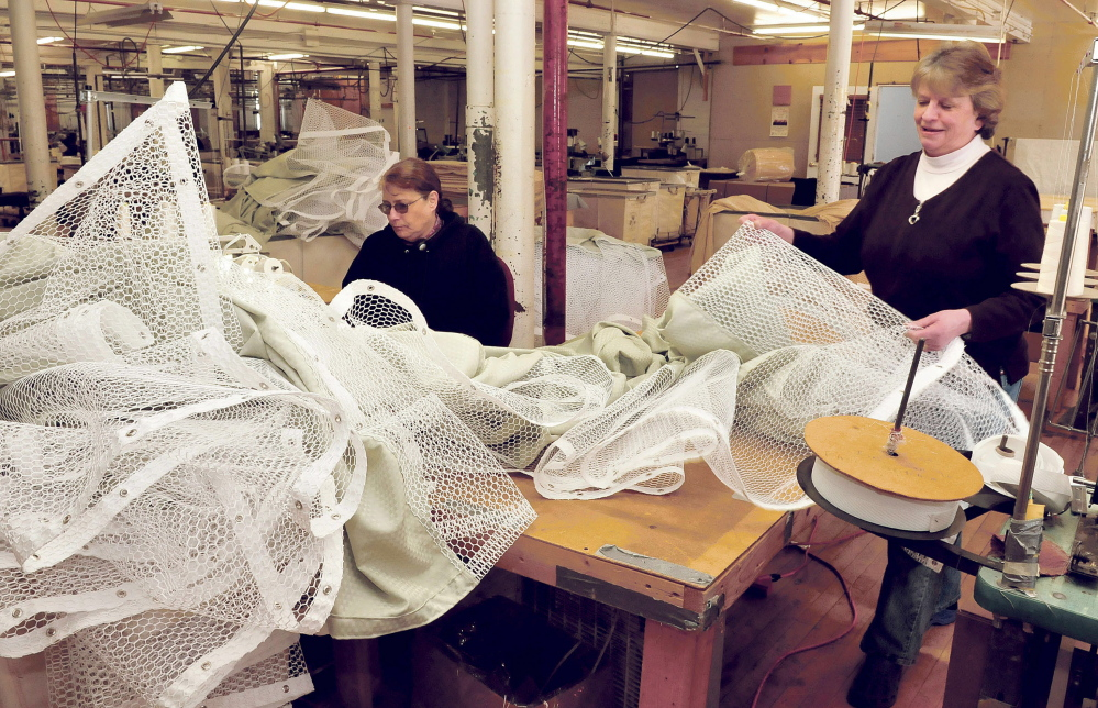 Maine Stitching Specialties employees Beth Moulton, left, and Cindy Laney work on medical privacy curtains made at the Skowhegan company.