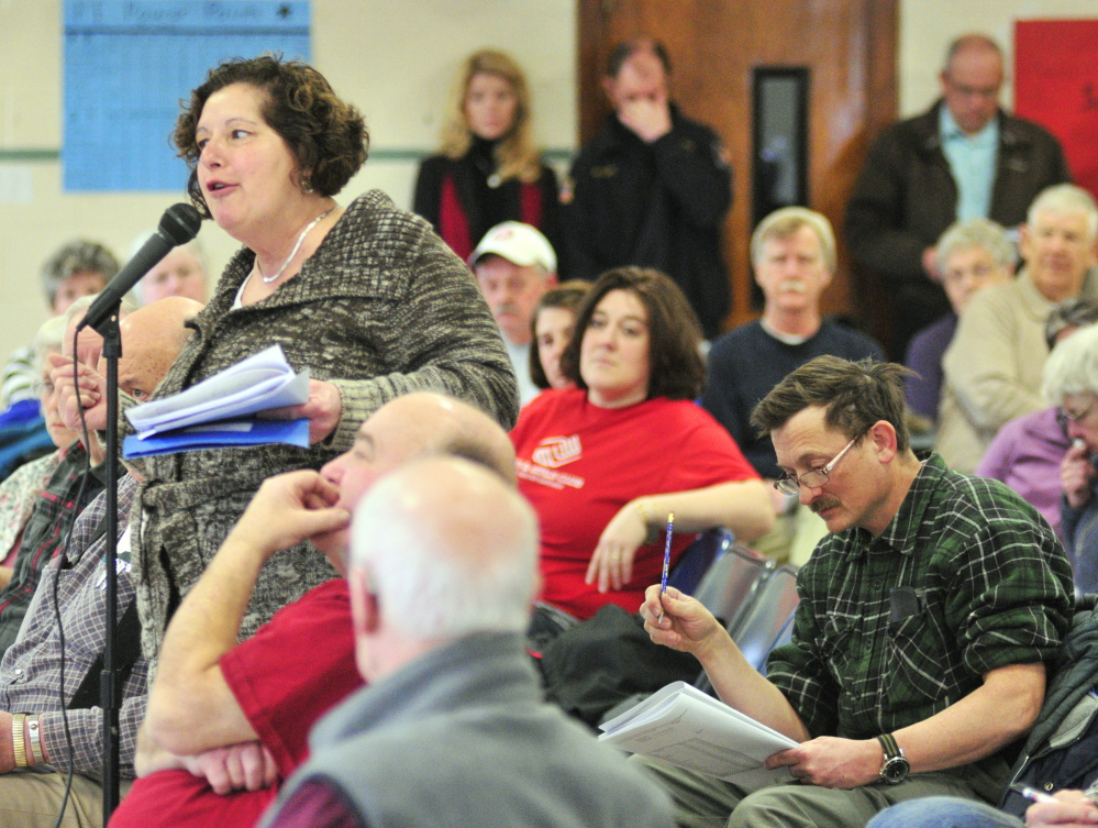 Gardiner Public Library Director Anne Davis, left, answers a question Saturday about Pittston's funding the library from Tim Lawrence, right, during the Pittston Town Meeting at the Pittston Consolidated School. Voters approved funding for the library.