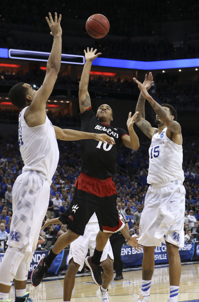 Cincinnati guard Troy Caupain shoots between Kentucky forward Trey Lyles, left, and forward Willie Cauley-Stein during the second half Saturday of an NCAA tournament game in Louisville, Ky. Kentucky won the game 64-51.