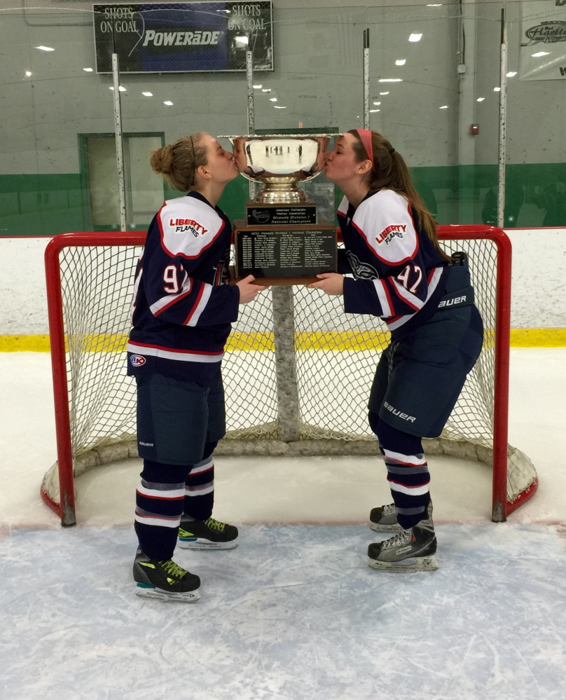 Winslow's Sarah Fowler, right, kisses the ACHA Division I championship trophy along with Liberty University teammate Courtney Gilmour. The Flames defeated Miami (Ohio) 4-1 on March 8 to win the title.
