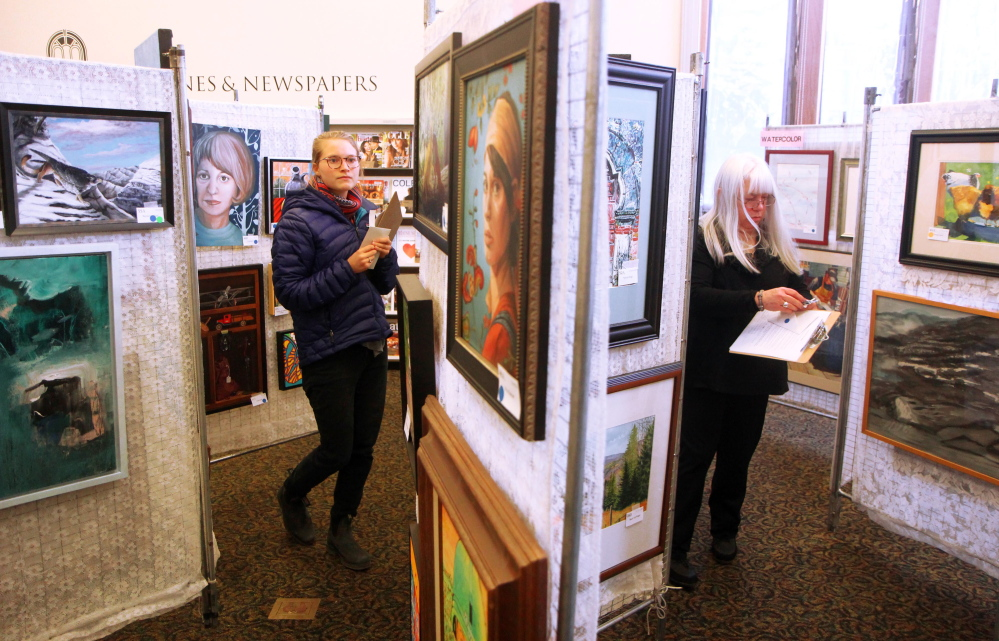 Ramey Mize, left, a Colby College Museum of Art curatorial fellow, judges pieces on Saturday for this week's 25th annual Maine Open Juried Art Show at the Waterville Public Library. At right is fellow judge Marsha Donahue of North Light Gallery in Millinocket.