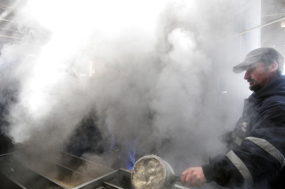 Jason Smith checks evaporating sap on Sunday at his family's sugar shack, Mike's Maple House, in Winthrop. The Smith family hosted the public on Maine Maple Sunday.