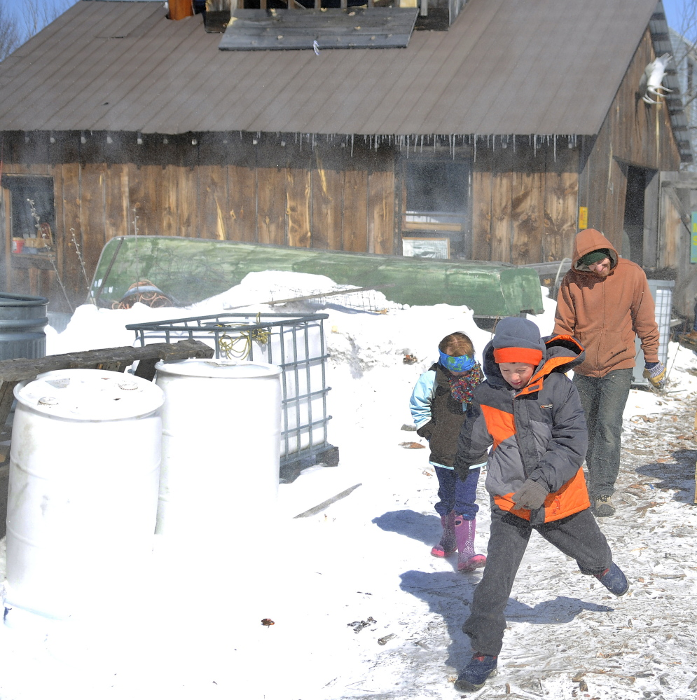Jaxon August, 8, leads his sister, Anna, 6, and father Ryan through gusts of wind Sunday outside Mike's Maple House in Winthrop. The sugar shack hosted the public on Maine Maple  Sunday.