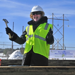 Sara J. Burns, president and chief executive officer of Central Maine Power, smiles after hammering in a ceremonial plaque into the last structure of the Maine Power Reliability Program on Monday in Windsor.