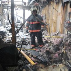 A firefighter inspects the remains of an apartment building Feb. 5 on Highland Avenue in Gardiner after a fire there displaced about 30 people.