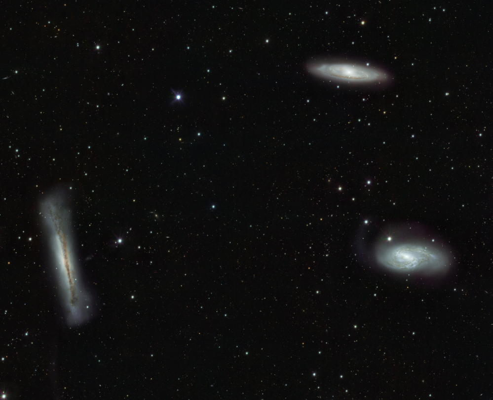 The Leo Triplet — NGC 3628, left; M66, bottom right; and M65, top right — three large spiral galaxies in the constellation Leo.