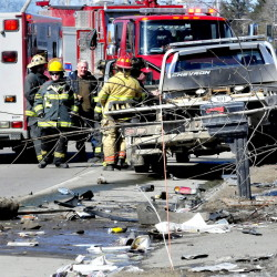 Firefighters and onlookers talk Tuesday as police reconstruct the scene of a fatal car accident on U.S. Route 201 in Madison.