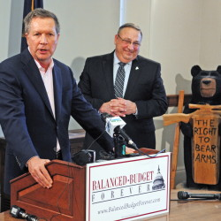 Ohio Republican Gov. John R. Kasich advocates for a constitutional amendment for a national balanced budget at the State House in Augusta on Thursday, with Maine Gov. Paul R. LePage at right.