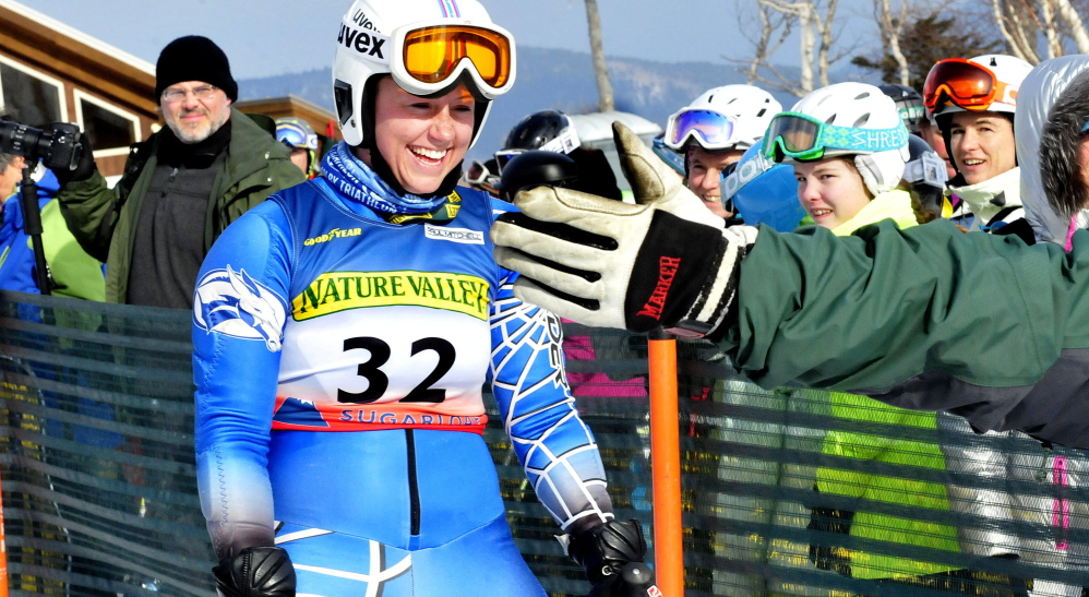 Colby College's Sierra Leavitt gets a high five from Stacy Patrick after her race during the U.S. Alpine Championships on Thursday at Sugarloaf Mountain.