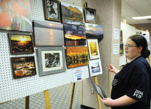 Becky Pass looks for a space to hang another landscape photo as she helps set up the art and woodcarving show Thursday, the day before the opening of the Maine Sportsman's Show at the Augusta Civic Center.