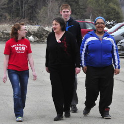 In an effort to motivate people to get exercise, students from Upper Kennebec Valley Memorial High School, New Balance Athletic Shoe Inc. and Bingham Area Health Center have distributed pedometers and vouchers for sneakers. Going for a walk and trying out the pedometer she received Thursday, Rose Mary Henderson, center, speaks with Ashley Brooks of New Balance and students Cody Laweryson and Courtney Mills.