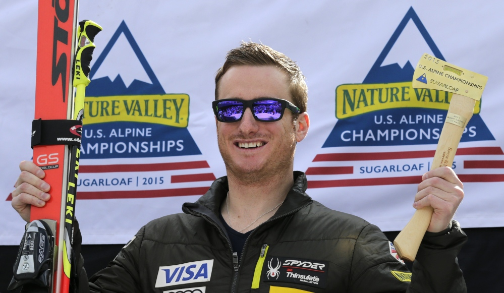 Tim Jitloff holds up his axe trophy and skis after winning the men's giant slalom race at the U.S. Alpine Ski Championships at the Sugarloaf Mountain Friday.