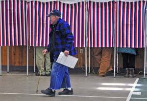 CAP.cutline_standalone:Howard Boston walks from a voting booth to put his ballot into a tabulating machine last Friday at the Center For All Seasons in Belgrade, where voters were asked to weigh in on an ordinance that would govern mass gatherings and to choose town officials. Boston, 92, is believed to be the town's oldest resident.