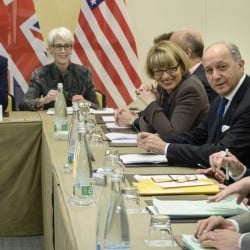 US Secretary of State, John Kerry, left, US Under Secretary for Political Affairs, Wendy Sherman, 2nd left, French Foreign Minister, Laurent Fabius, right, and others wait for the start of a trilateral meeting at an hotel in Lausanne Saturday.