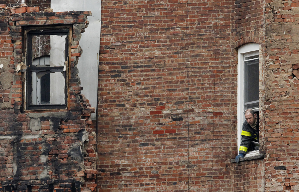 A fire official stands at the window of a building adjacent to the site of a building collapse in the East Village neighborhood of New York.