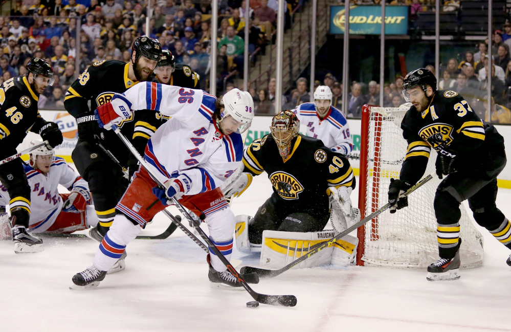 New York Rangers right wing Mats Zuccarello, 36, looks to pass in front of the goal as Boston Bruins goalie Tuukka Rask, 40, defenseman Zdeno Chara, 33, and center Patrice Bergeron, 37, keep an eye on the puck during the first period Saturday in Boston.