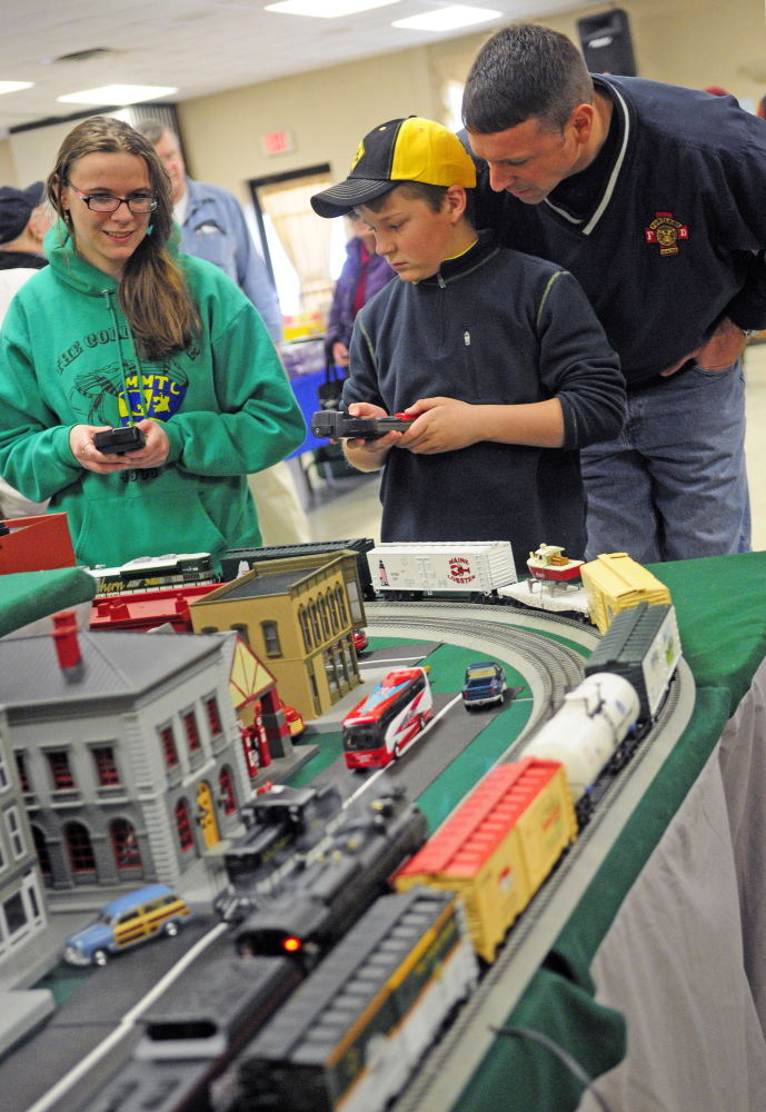 Mary Wunderlich, of Oakland, left, and Jackson Small, of Cumberland, use handheld remotes to control trains during the Maine3Railers model railroad show on Saturday at the Elks Club in Augusta. Small's father, Dan, watches at right.