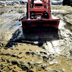 Jim Boivin uses the bucket of his tractor to smooth the ruts out of a muddy portion of a parking lot at Tracy's Kountry Kitchen on Wednesday, a new restaurant that opened Thursday.